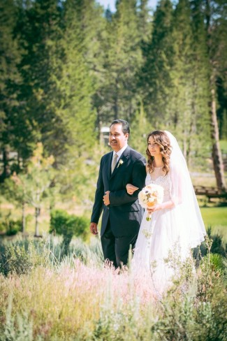 20 ourdoor wedding ceremony in Sierra Nevada mountains bride walking down aisle with farther in illusion bridal gown