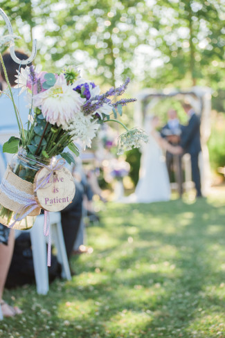 21 Green Villa Barn & Gardens, Oregon wedding ceremony with aisle decor flowers with wooden sign that says love is patient