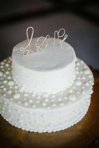 outdoor wedding reception in Sierra Nevada mountains white cake with love cake topper