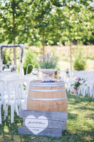 wedding ceremony seating with wine barrel and lavender decor on top, wood planks with heart painted on front