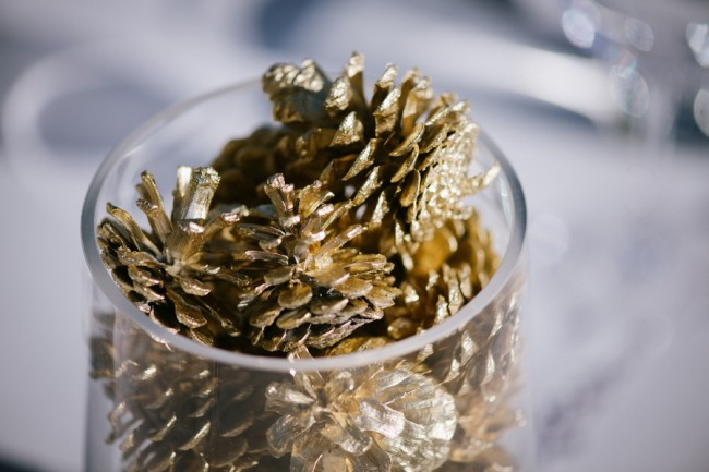 Ourdoor wedding reception in Sierra Nevada mountains gold pine cones sparkly in white vase