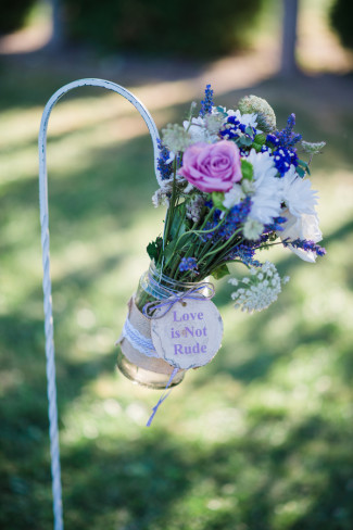 """Green Villa Barn & Gardens wedding with aisle decor flower arrangement and a wooden saying """"Love is not rude"""""""