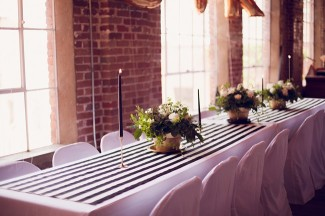 29 reception table with black and white strip table runner and black candles with gold flower vases