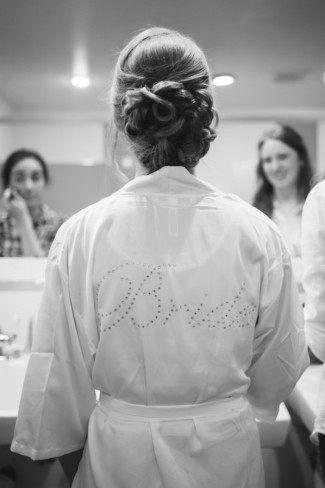 """Bride wearing a white silk robe with rhinstone word """"bride"""" on the back"""
