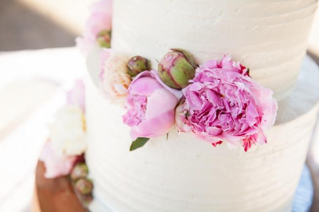 white wedding cake with pink carnations adorning