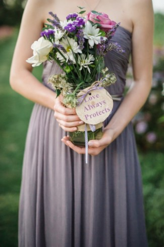 bridesmaid in purple dress holding purple pink and white bouquet and a sign saying love always protects