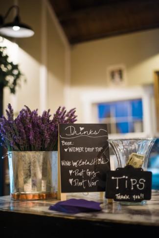 Chalkboard sign drink menu with fresh lavender in tin vase at wedding reception at Green Villa Barn & Gardens