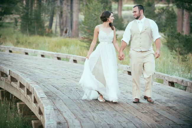 Woodsy Wedding with Pine Cone Details in Tahoe - bride and groom walking over bridge holding hands