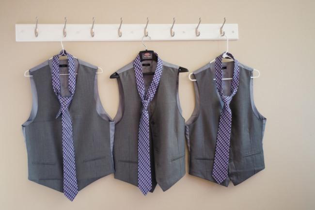 three gray vests and purple ties hanging on wall at Green Villa Barn & Gardens wedding