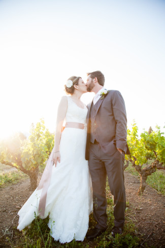 Bride and groom kiss standing in front of vineyard at Guglielmo Winery