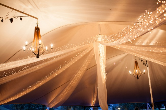 Inside of wedding tent with chandeliers and mini lights