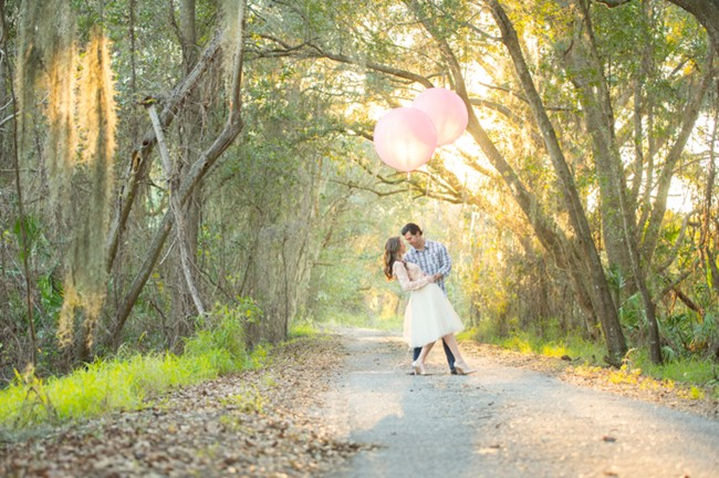 5 3 Maternity photo couple standing on path with pink geronimo baloons