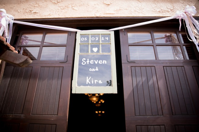 wedding ceremony entrance sign between two large wood doors at Guglielmo Winery wedding