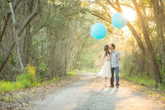 6 3 Maternity photo couple standing on path with 2 blue geronimo balloons