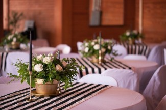 9 wedding reception tables with black and white striped table cloths gold flower vases and black candles