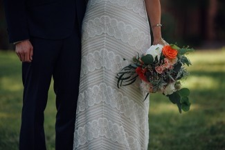 Bride and groom standing together with pink and orange peonie bouquet