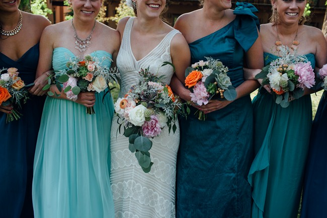 Bride standing with bridesmaids in teal color dresses and pink and orange peonie bouquets
