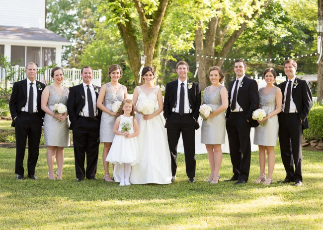 Bride with bridesmaids in grey dresses and groomsmen with black suits and ties at the reserve at oak bowery bride wearng tara keely wedding dress