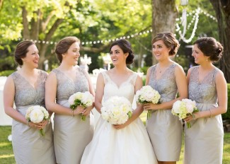 Bride with bridesmaids in grey dresses at the reserve at oak bowery bride wearng tara keely wedding dress