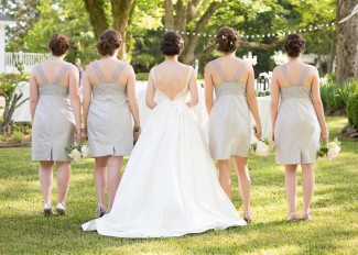 Bride with bridesmaids in grey dresses at the reserve at oak bowery bride wearng tara keely wedding dress standing with their back to the camera