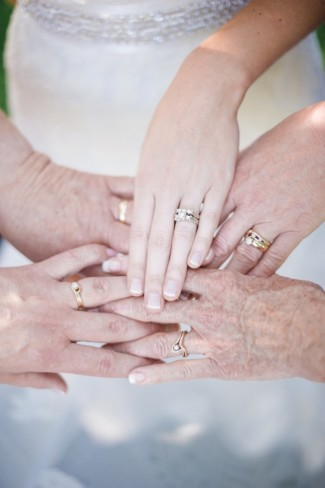5 women's hands together showing off their wedding rings