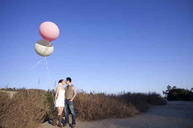 engagement shoot couple holding two giant balloons