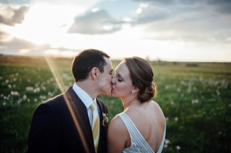 bride and groom kissing in field with sun shinning in back ground