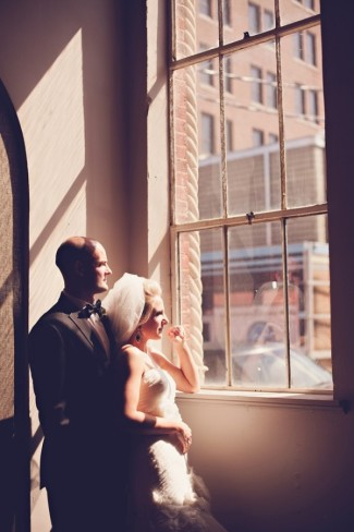 bride and groom stading near window