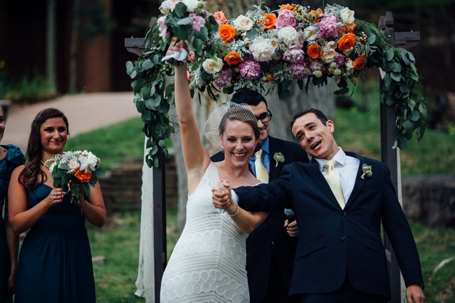 bride and groom walking down aisle in outdor ceremony with orange and pink and white floral arbor
