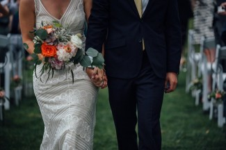 bride and groom walking down the aisle after getting married holding white and orange bridal bouquet