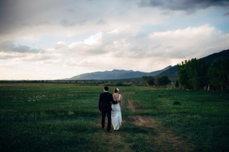 bride and groom walking outside in field in new mexico with mountain it back