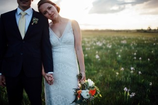 bride resting head on grooms shoulder in field outside carrying orange pink and white bridal bouquet with peonies
