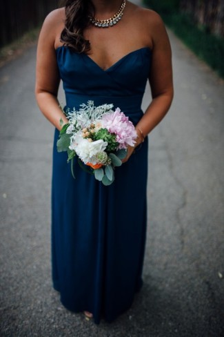 bridedmaids wearing blue dress carrying pink peony bouquet
