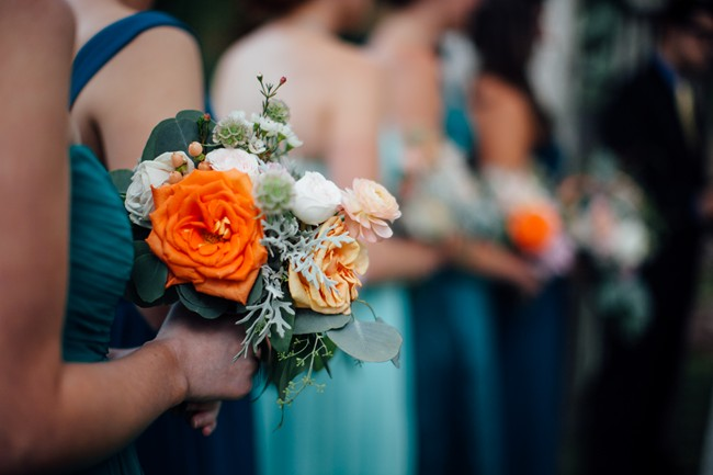 bridesmaids wearing green dresses carrying orange and pink bouquets