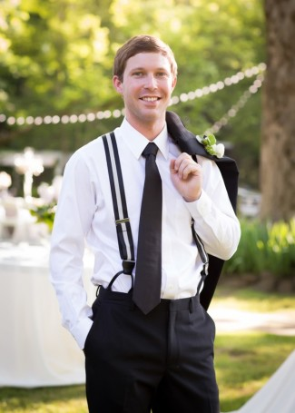 groom in black and white suite and suspenders at the reserve at oak bowery