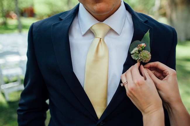 groom wearing yellow tie; pinning on his succulent boutonniere