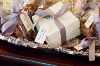 little boxes and bags of pecans, topped with a satin ribbon and personalized labels at wedding at the reserve at oak bowery