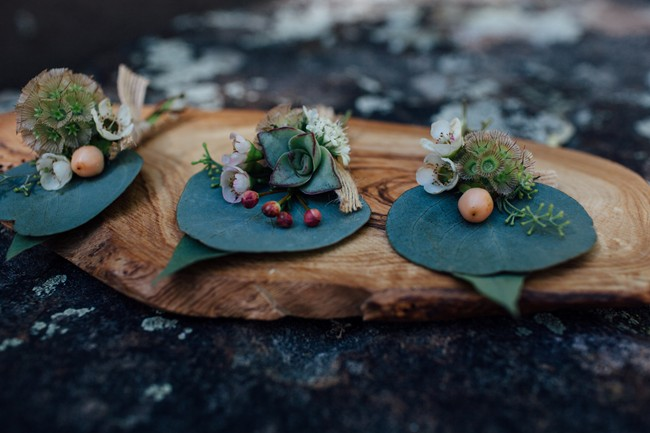 three succulent boutonnieres on wooden slab