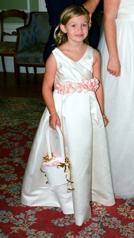 flower girl in white dress with pink sash belt