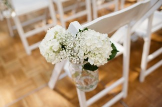 White folding chair with white hydrangea and baby's breath in mason jar hanging from chair