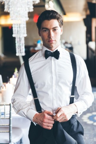 Groom wearing tux with black bow tie and black suspenders