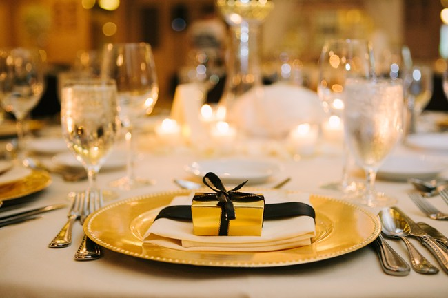 Wedding reception place setting with gold charger, white napkin, a gold box tied with a black bow