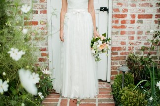Bride standing on brick path in the garden with peach, white bridal bouquet