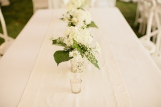 White and green floral centerpieces and small votive candles