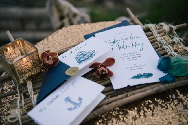 Nautical themed invitations with blue envelopes and writing. Gold speckled candle on gold sequin table cloth