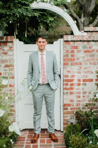 Groom standing next to brick wall