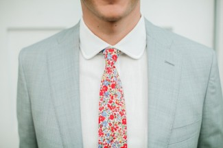 groom in gray suit and red, pink, blue floral tie