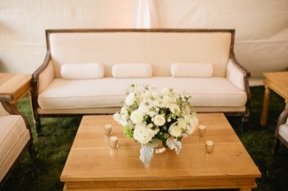 white furniture and white floral center piece under white tent for backyard wedding