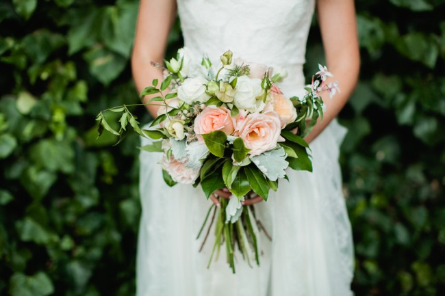 Bride carrying pink roses, white and green foliage bridal bouquet