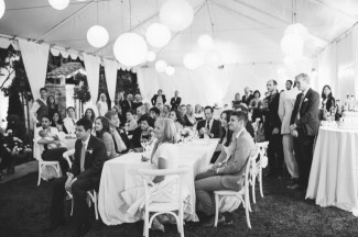 Backyard wedding reception sitting under white tenet with lanterns